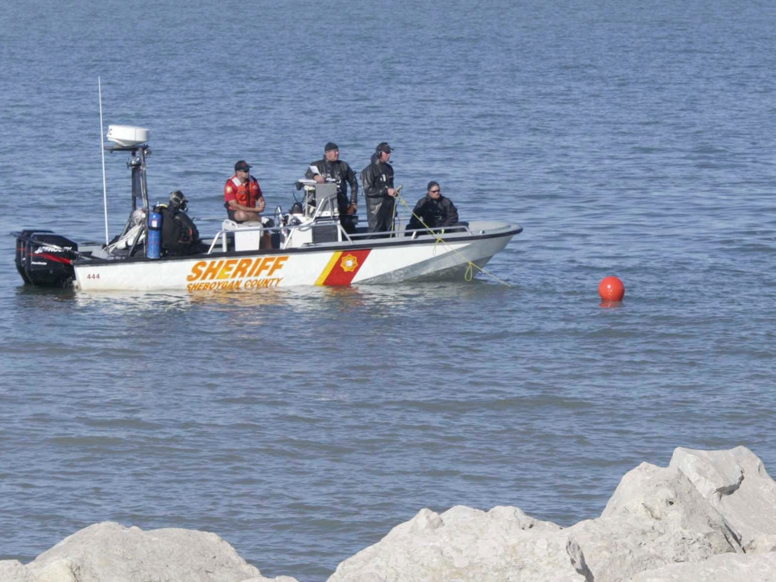Rescue officials and a scuba diver scan the waters of the Sheboygan, Wis. lakefront on Aug. 11, 2008, for John Duong. Duong, 15, of 2623 N. 36th St., was swept underwater by high waves Saturday afternoon while swimming with four friends at North Beach at Deland Park.   FILE PHOTO