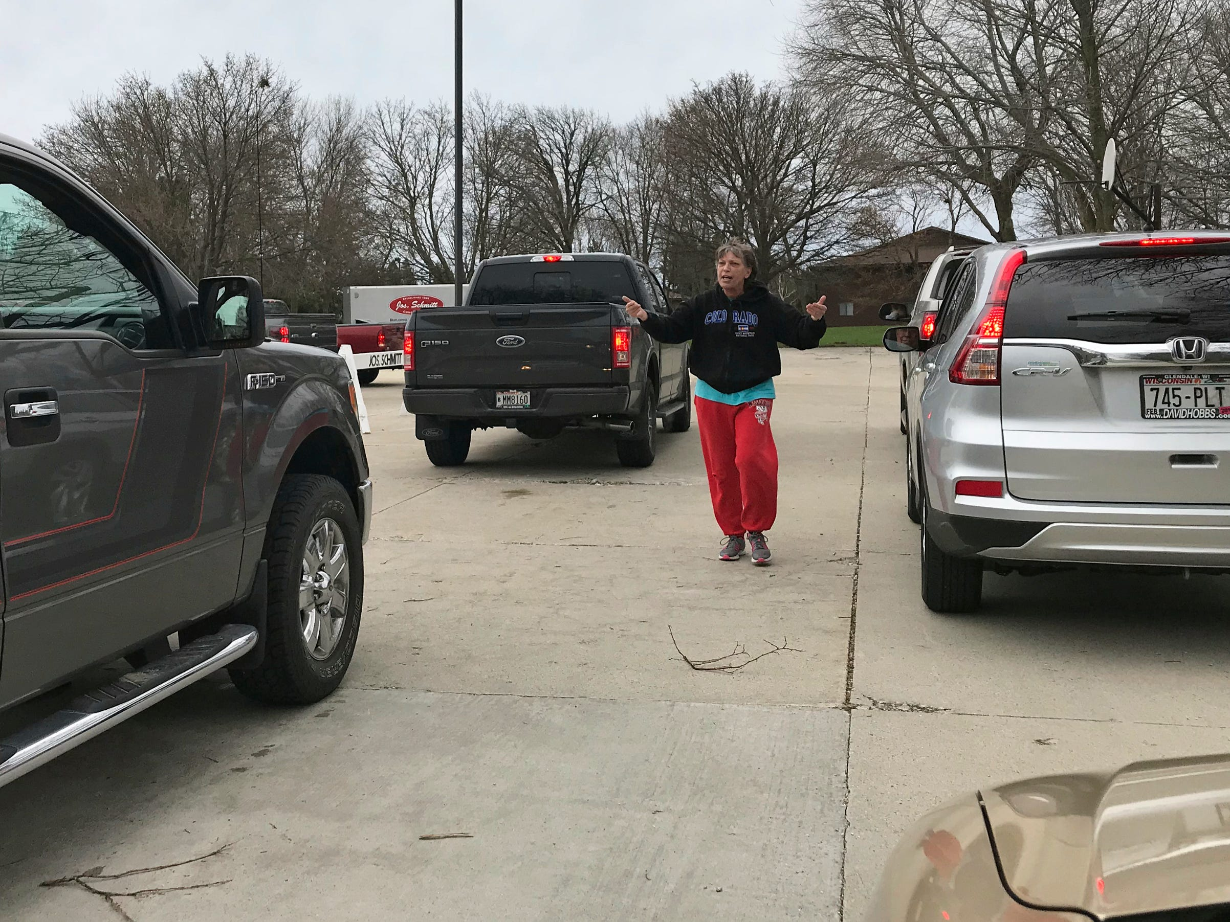A volunteer directs traffic at the recycling event at Ebenezer United Church of Christ, Saturday, April 27, 2019, in Sheboygan, Wis.