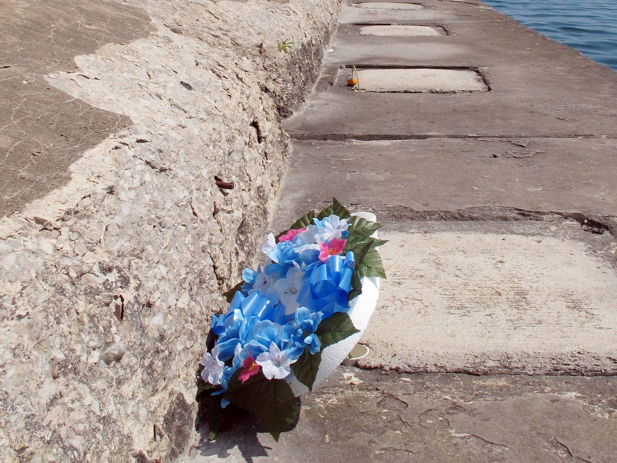A memorial appears on North Pier Aug. 14, 2012, in memory of David Diener, 21, and Kurt K. Netzer, 37, who lost their lives after being swept off of North Pier Aug. 10, 2012, in Sheboygan, Wis.  FILE PHOTO