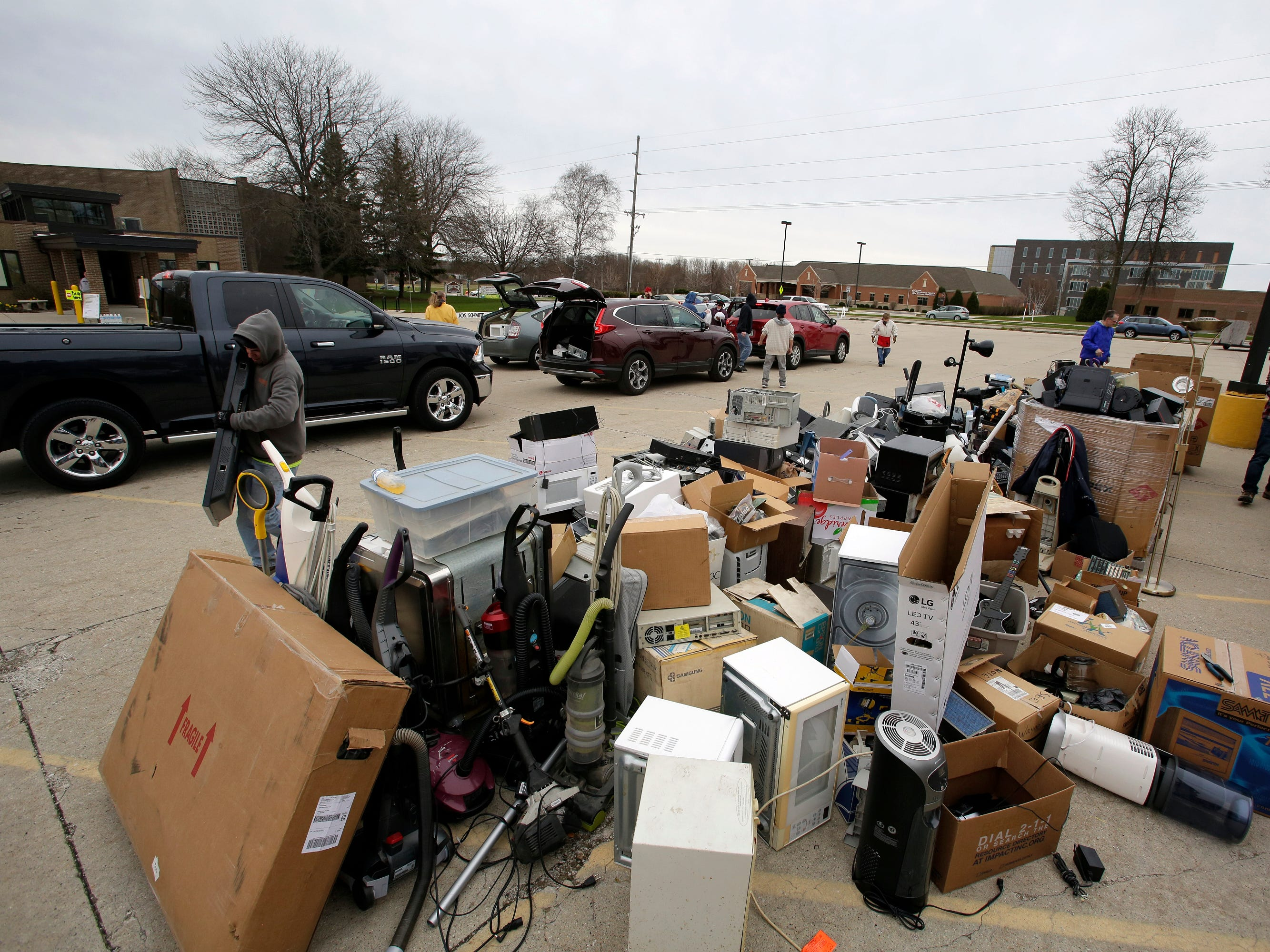 Piles of electronics of many types sit in a pile during a recycling event at Ebenezer United Church of Christ, Saturday, April 27, 2019, in Sheboygan, Wis.