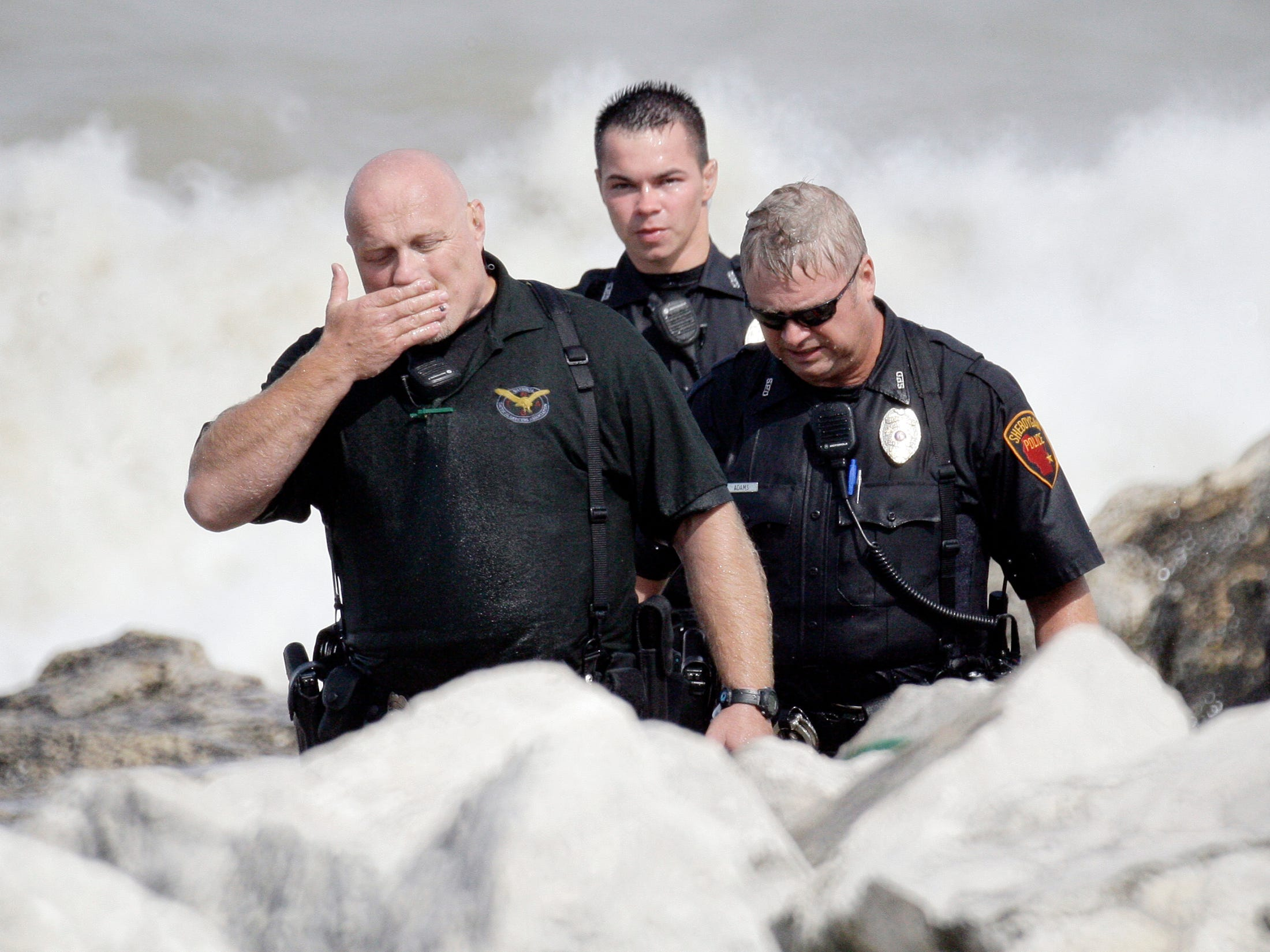 Emotions hit an officer at the scene of a search Aug. 10, 2012, in Sheboygan, Wis.  FILE PHOTO