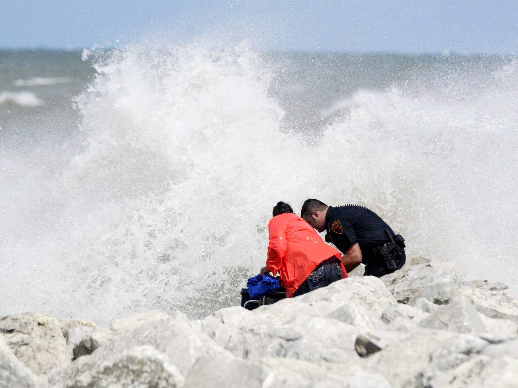 A Sheboygan police officer escorts a woman who was rescued from the North Pier on Aug. 10, 2012, in Sheboygan, Wis.  FILE PHOTO