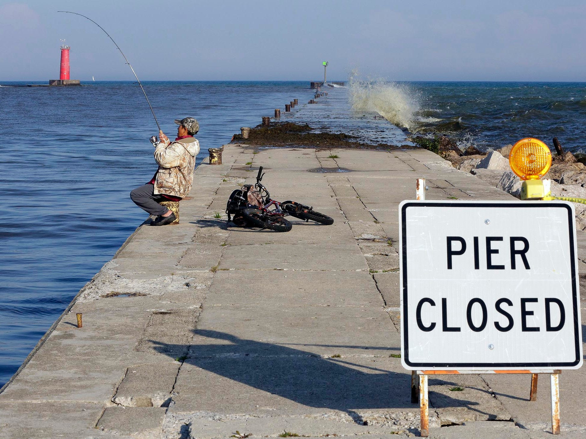 A fisherman works with his rod on the dry part of South Pier, which was closed by officials due to strong waves Oct. 5, 2016, in Sheboygan, Wis.  FILE PHOTO