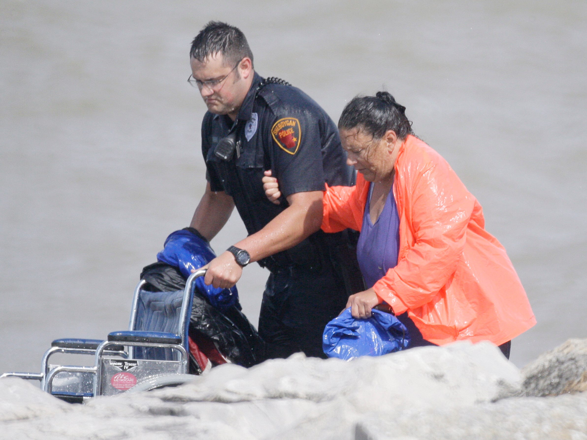 A Sheboygan first responder escorts a woman who was rescued from the North Pier on Aug. 10, 2012, in Sheboygan, Wis.  FILE PHOTO