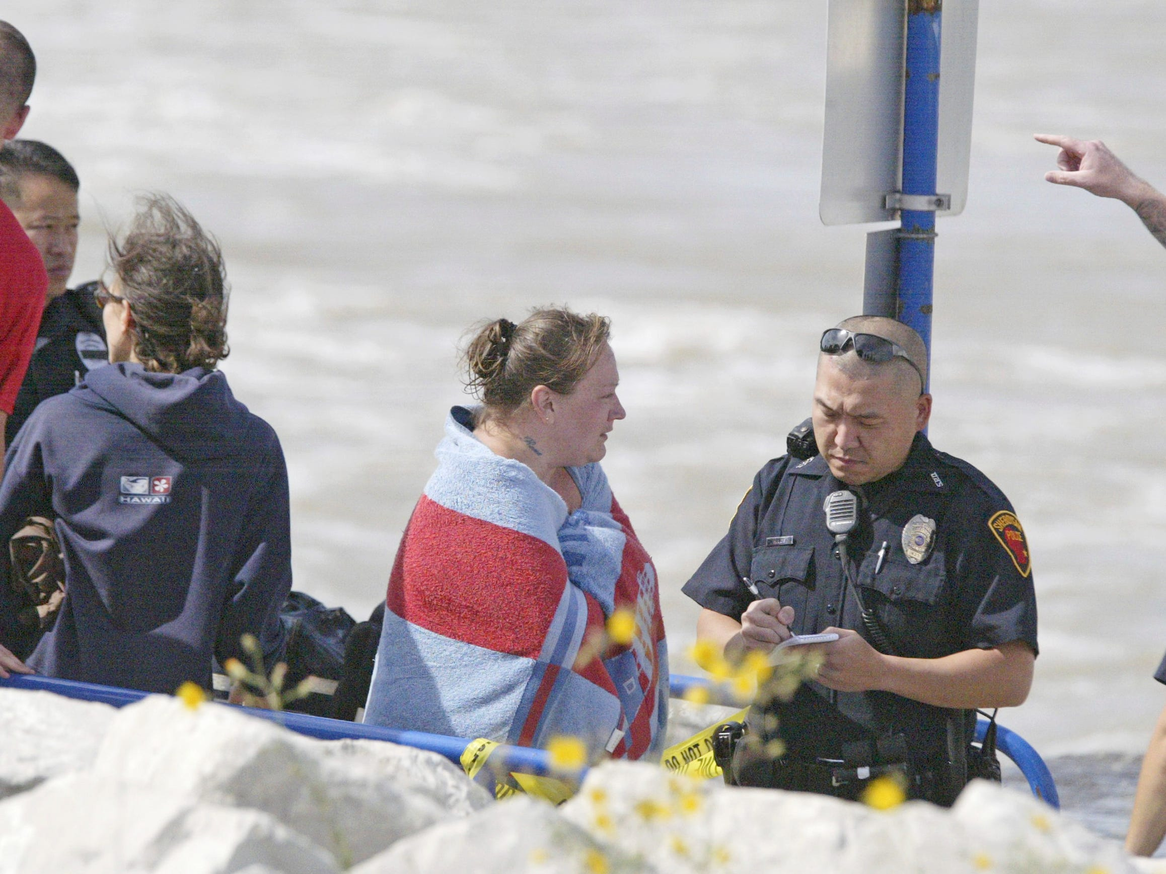 Police interview one of the rescued persons Aug. 10, 2012, near North Pier in Sheboygan, Wis.  FILE PHOTO