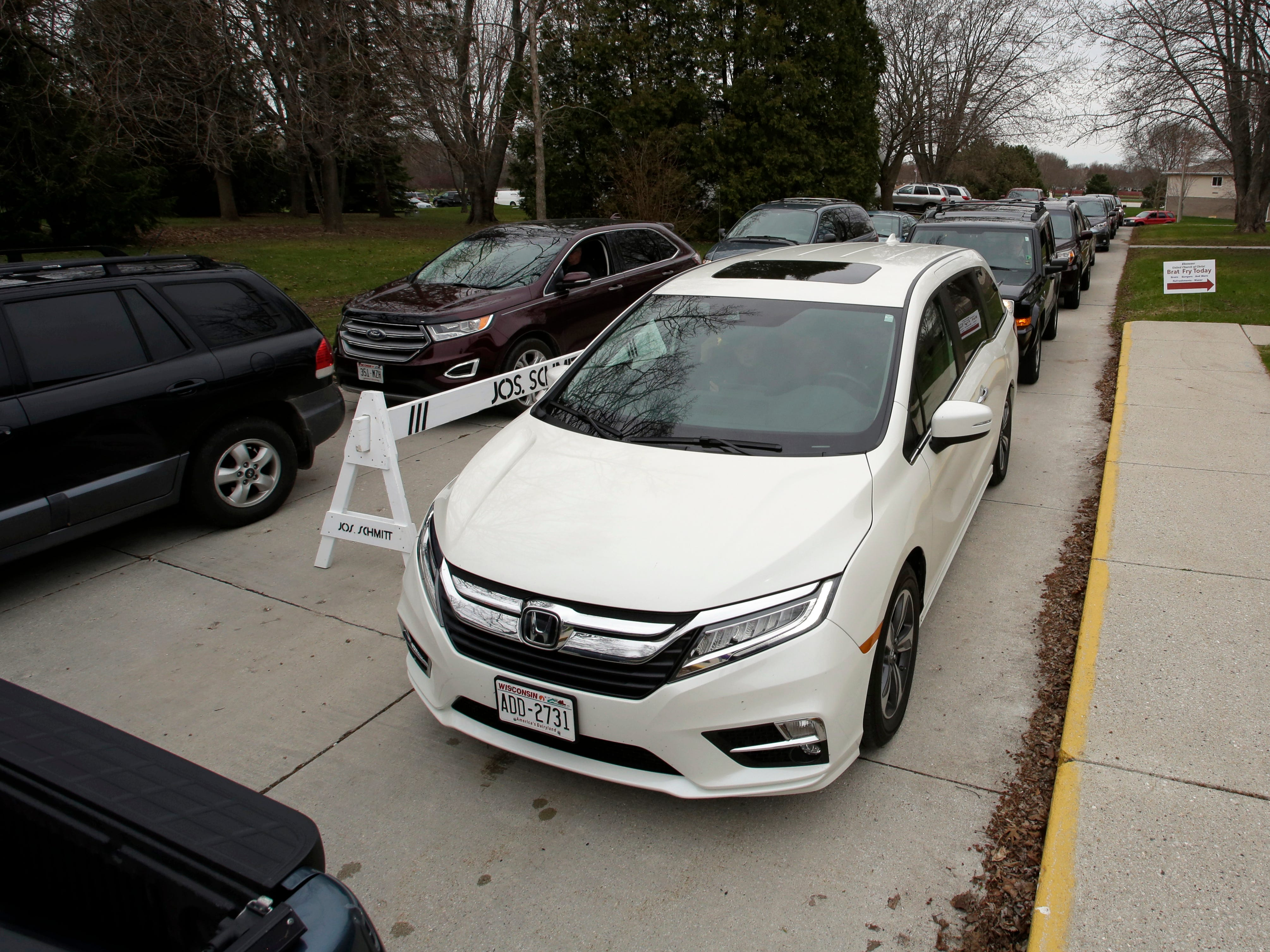 Vehicles wait in line at a recycling event at Ebenezer United Church of Christ, Saturday, April 27, 2019, in Sheboygan, Wis.