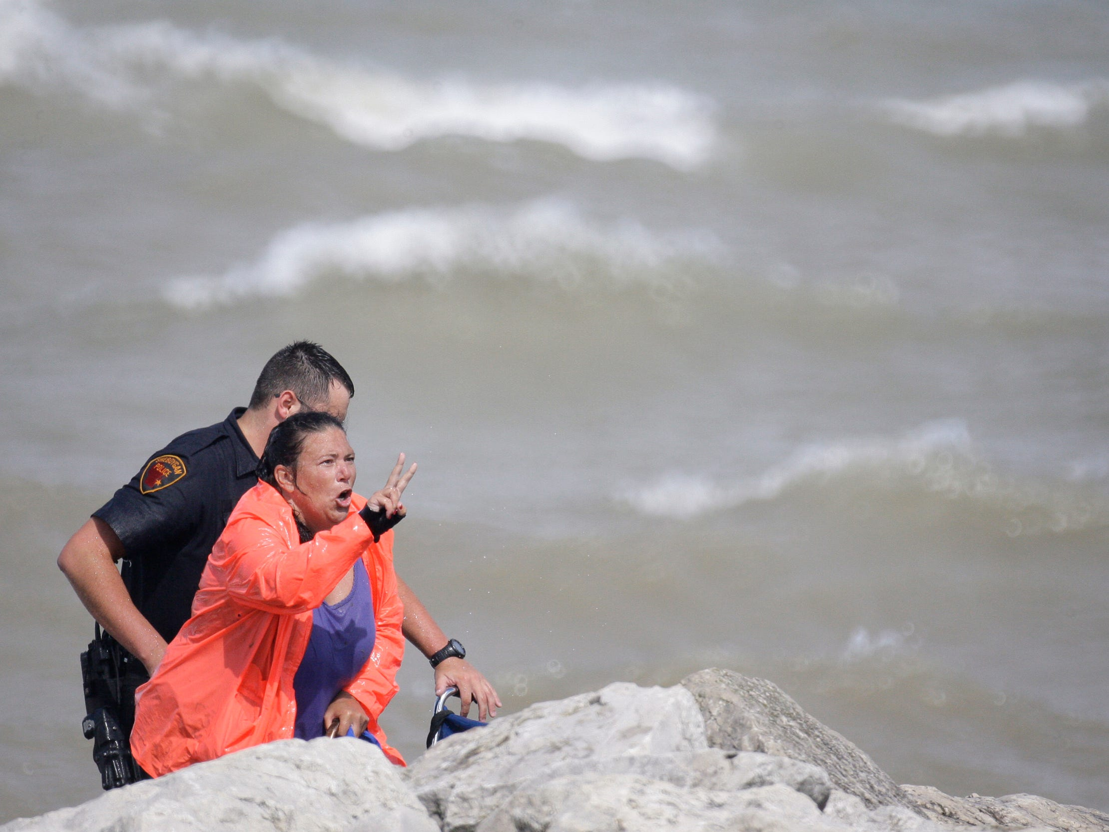 A rescued woman communicates with law enforcement Aug. 10, 2012, in Sheboygan, Wis., near the North Pier.  FILE PHOTO