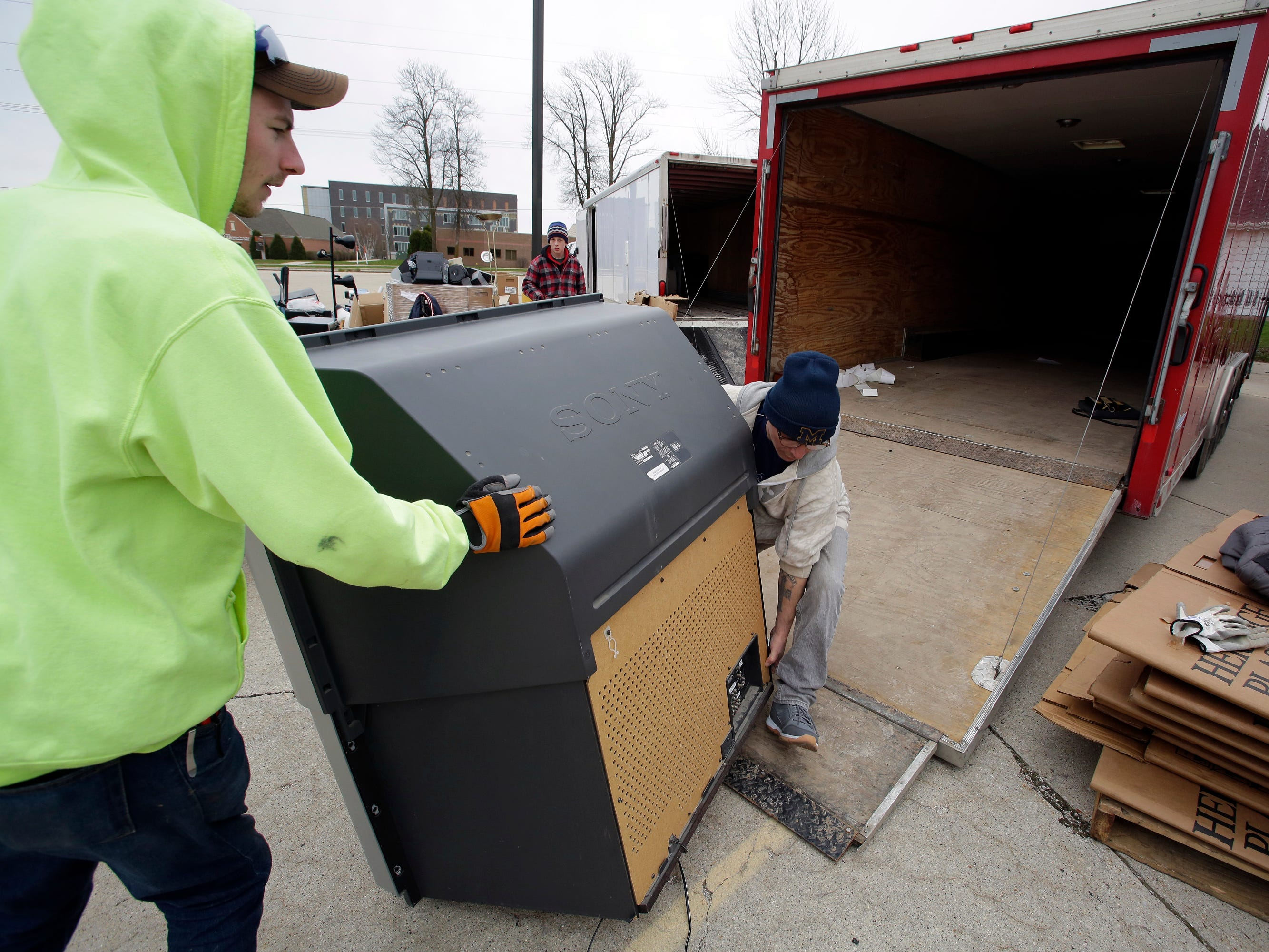 Tanner Gumm of Johnsonville, left, and Ron Howser of Sheboygan move a large screen television during a recycling event at Ebenezer United Church of Christ, Saturday, April 27, 2019, in Sheboygan, Wis.