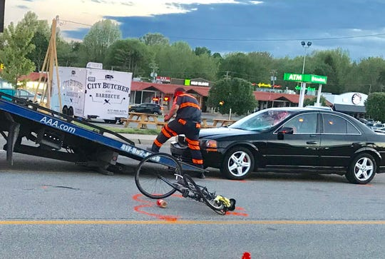 A tow truck operator works to remove a car with a shattered windshield, which is right next to a bicycle that is in the middle of Sunshine Street. This photo was taken shortly after a cyclist was hit by a vehicle.