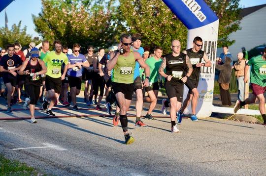 Runners cross the starting line of the Park to Park Half Marathon from Stuarts Draft Park to Waynesboro's Ridgeview Park on Saturday, April 27.