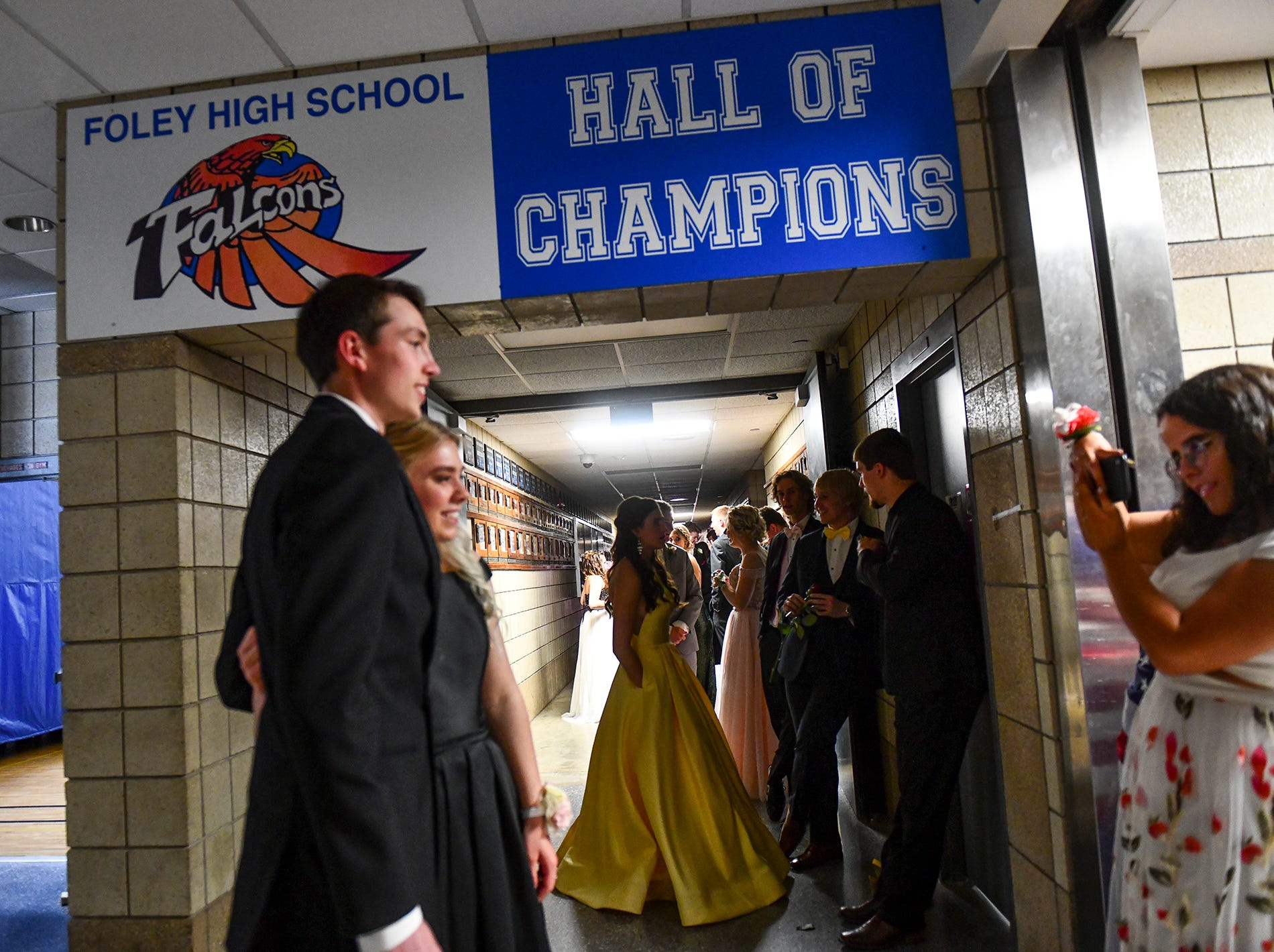 Couples pose for photos before taking their turn at the prom grand march route Saturday, April 27, at Foley High School.