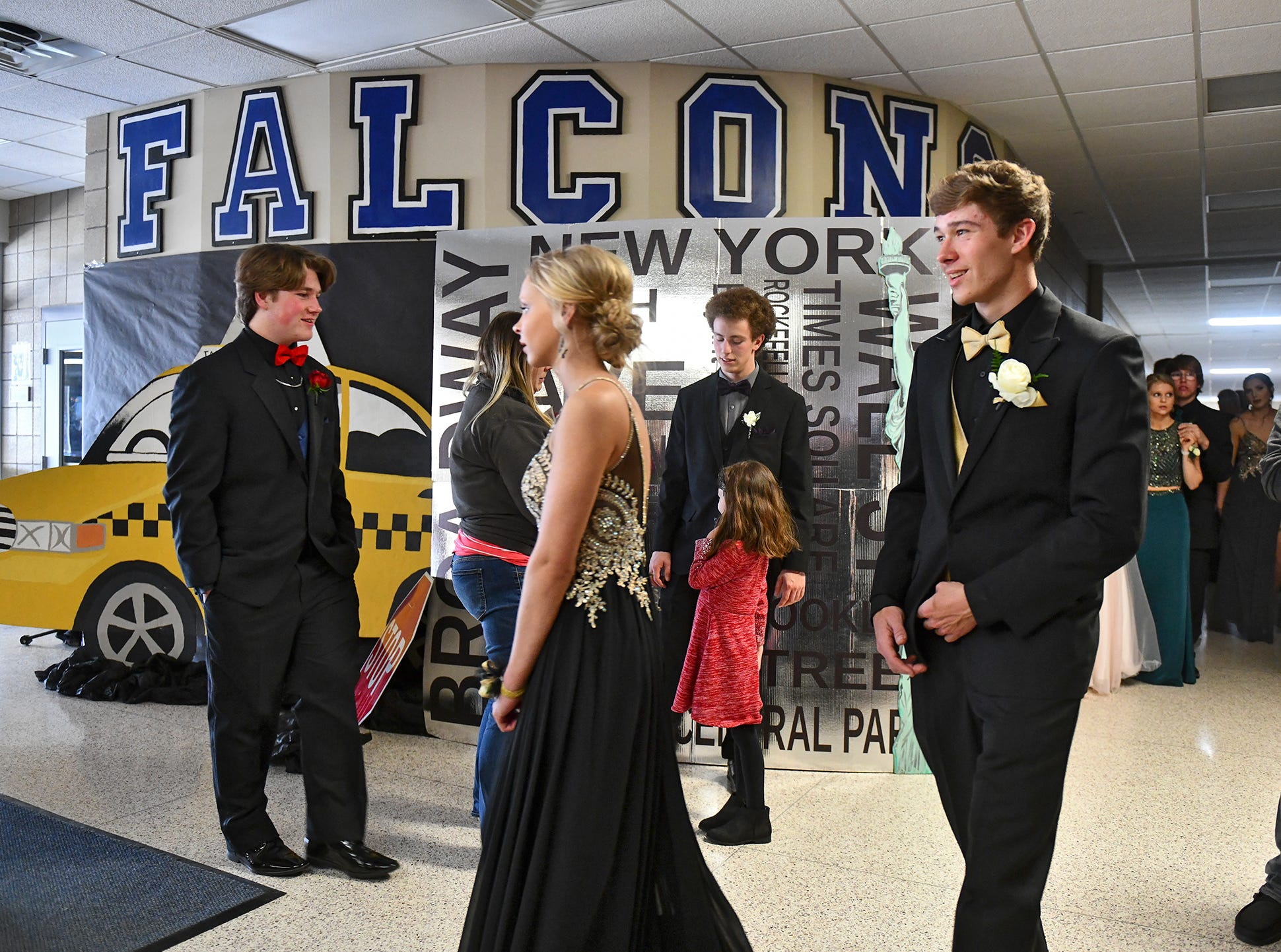 Couples walk past themed backgrounds during prom Saturday in Foley.