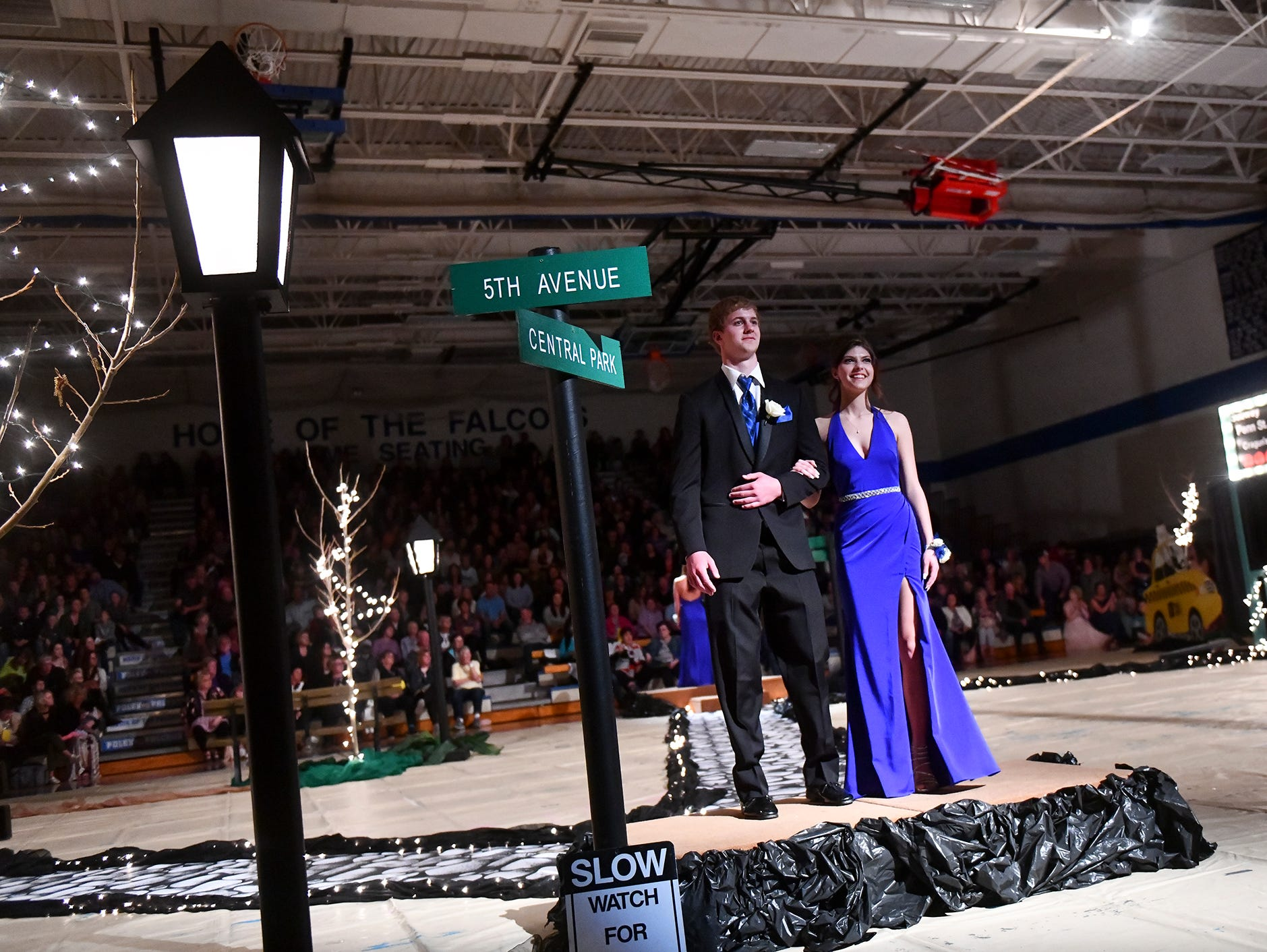 Couples smile while walking down the prom grand march route Saturday, April 27, at Foley High School.