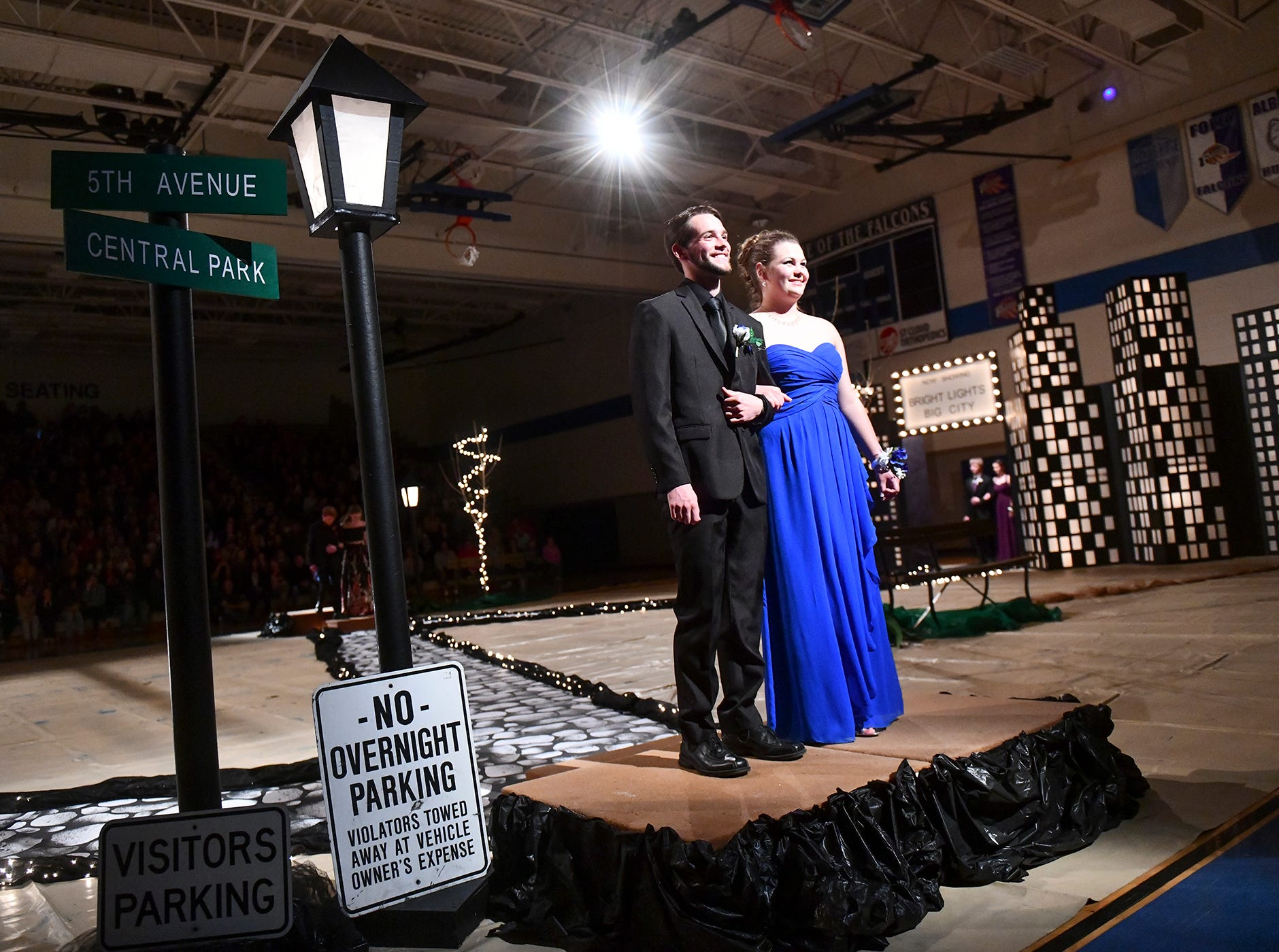 A couples smiles while walking down the prom grand march route Saturday, April 27, at Foley High School.