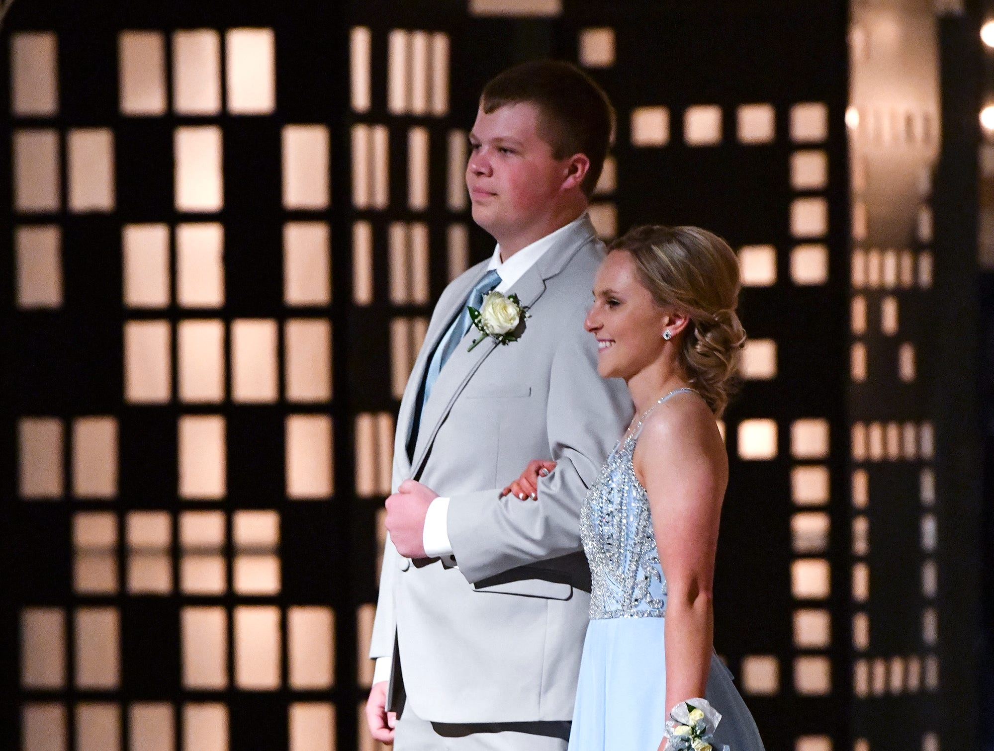 Couples pose for photos while walking down the prom grand march route Saturday, April 27, at Foley High School.