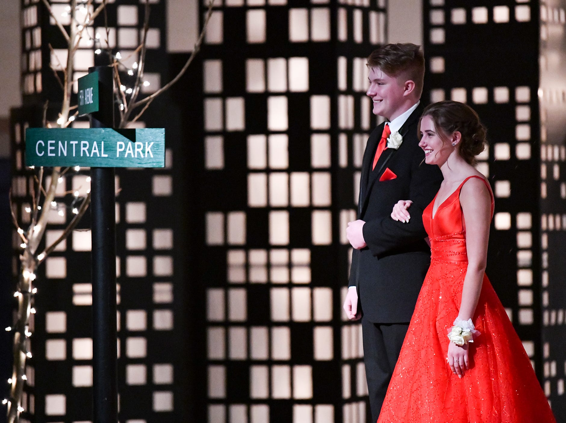 Couples smile for photos while walking down the prom grand march route Saturday, April 27, at Foley High School.