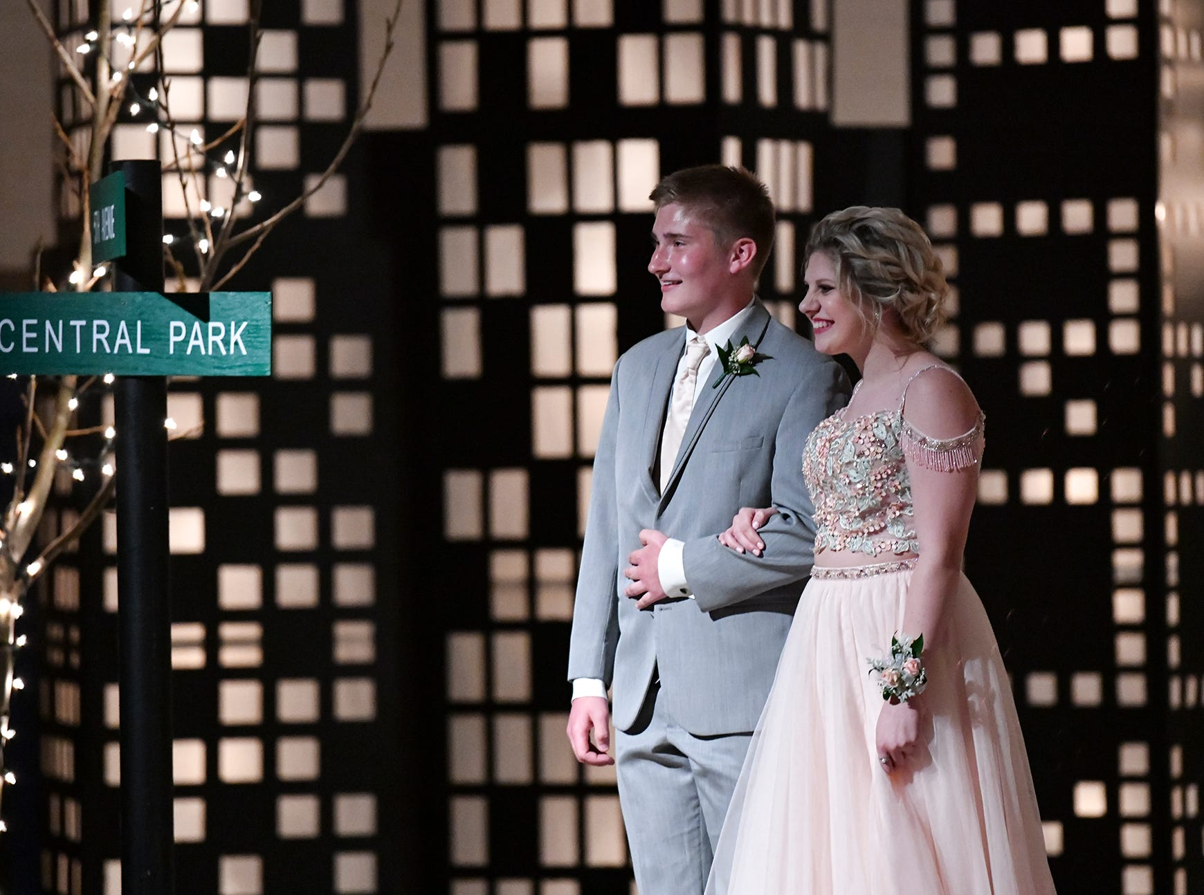 Couples smile against a city background while walking down the prom grand march route Saturday, April 27, at Foley High School.