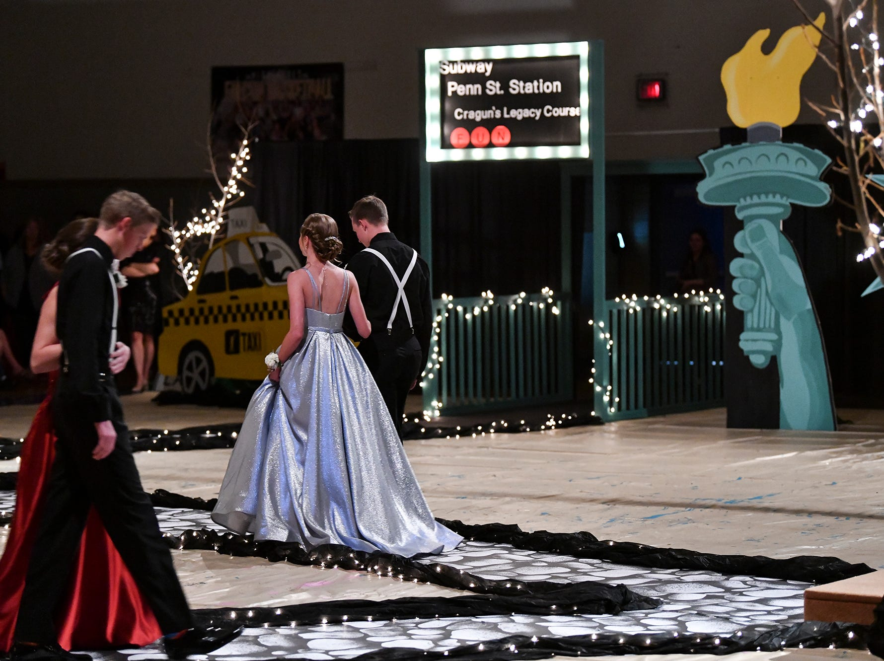 Couples walk down the prom grand march route Saturday, April 27, at Foley High School.