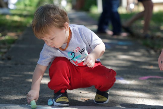 Giovanni Conetta, 1, draws on the sidewalk with chalk. Art lovers enjoy the work of fine art painters, photographers, sculptors and other unique artists at the LeMoyne Chain of Parks Art Festival Saturday, April 27, 2019.