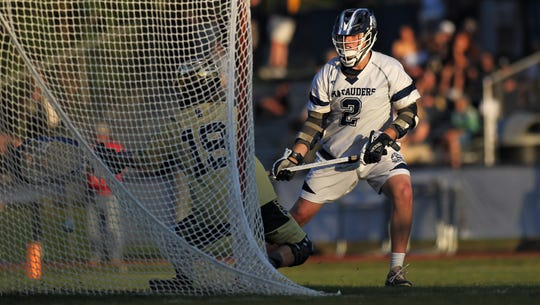 Maclay junior Sam Chase sets up Gulf Breeze keeper Garrison Story for a goal as Maclay beat Gulf Breeze 18-8 in a lacrosse regional quarterfinal playoff game on April 26, 2019.