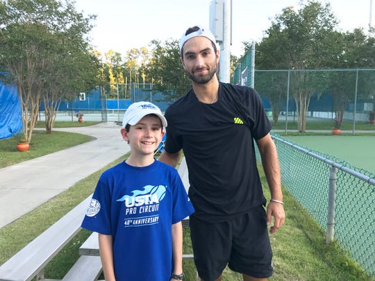 Owen Wright (left) works as a ball boy at the Tallahassee Tennis Challenger. He poses with Noah Rubin after the tennis player signed his cap.
