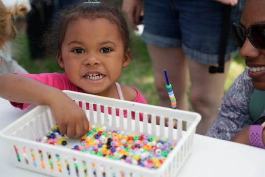 Rahiyla Ameh El, 2, smiles as she makes her own bracelet. Art lovers enjoy the work of fine art painters, photographers, sculptors and other unique artists at the LeMoyne Chain of Parks Art Festival Saturday, April 27, 2019.