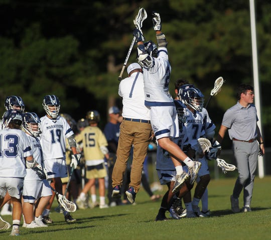 Maclay lacrosse coach Justin VanTassel and junior Sam Chase celebrate during a timeout as Maclay beat Gulf Breeze 18-8 during a lacrosse regional quarterfinal playoff game on April 26, 2019.