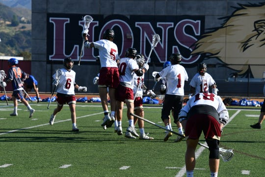 Oaks Christian's Mike Spaeth (5) and Ronny Redell celebrate a goal in Friday's boys lacrosse win over visiting Westlake.