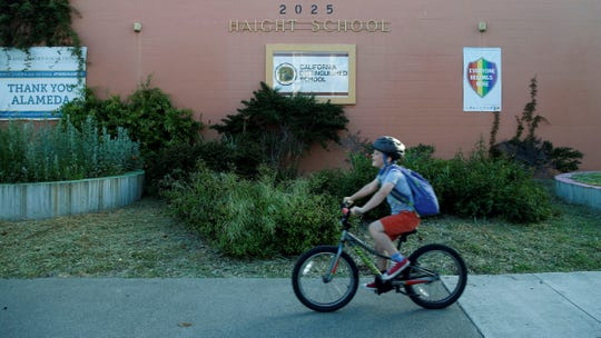 In this Thursday photo, a student arrives for a day of classes at Haight Elementary School on a bicycle in Alameda. School district officials are changing the name of the school to Love Elementary after it was discovered that former California Gov. Henry H. Haight had racist tendencies.