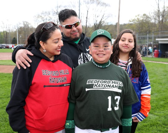 Rocky Serrano Jr. with his mother Marivel and father Rocky, as sister Allison looks on, during the opening day of the Bedford Hills Katonah Little League at Bedford Hills Memorial Park, April 27, 2019. Rocky Jr. suffered a stroke in July 2018, and had to battle his way back onto the field. He was given the honor of throwing out the first pitch to start the season.