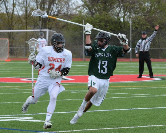 Yorktown defenseman Keith Boyer (13) prepares to lower the boom following a face-off win by Somers midfielder Conor Jaykus on Saturday, April 27, 2019. The Huskers built a comfortable early lead and hung on for the 9-5 win.
