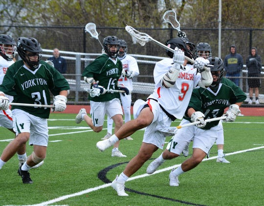 Somers attackman Nick Rossi (9) rolls back and fires against Yorktown on Saturday April 27, 2019.