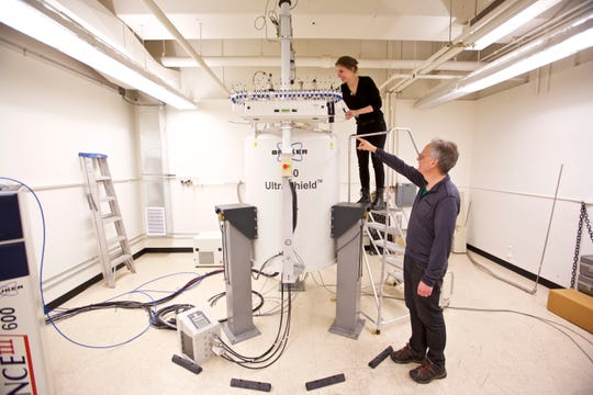 Graduate student Anna Duell, top, and Dr. David Peyton collect samples from a nuclear magnetic resonance spectrometer in a lab at Portland State University in Portland, Ore., Tuesday, April 16, 2019. Peyton co-authored a study analyzing the concentration of Juul's full-strength pod against nine other nicotine formulas on the market in 2017. Juul's nicotine level dwarfed its competitors, in some cases by twentyfold. (AP Photo/Craig Mitchelldyer)