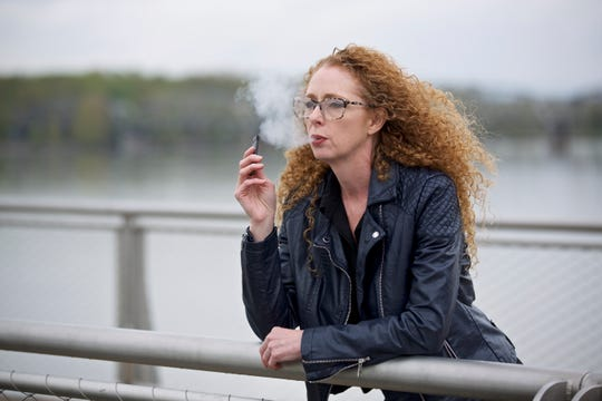 Chantel Williams vapes from a Juul pen in Vancouver, Wash., Tuesday, April 16, 2019. She tried gums, patches and various electronic cigarettes to quit smoking. What finally worked for Williams was the small, reusable e-cigarette that has a strong nicotine punch. (AP Photo/Craig Mitchelldyer)