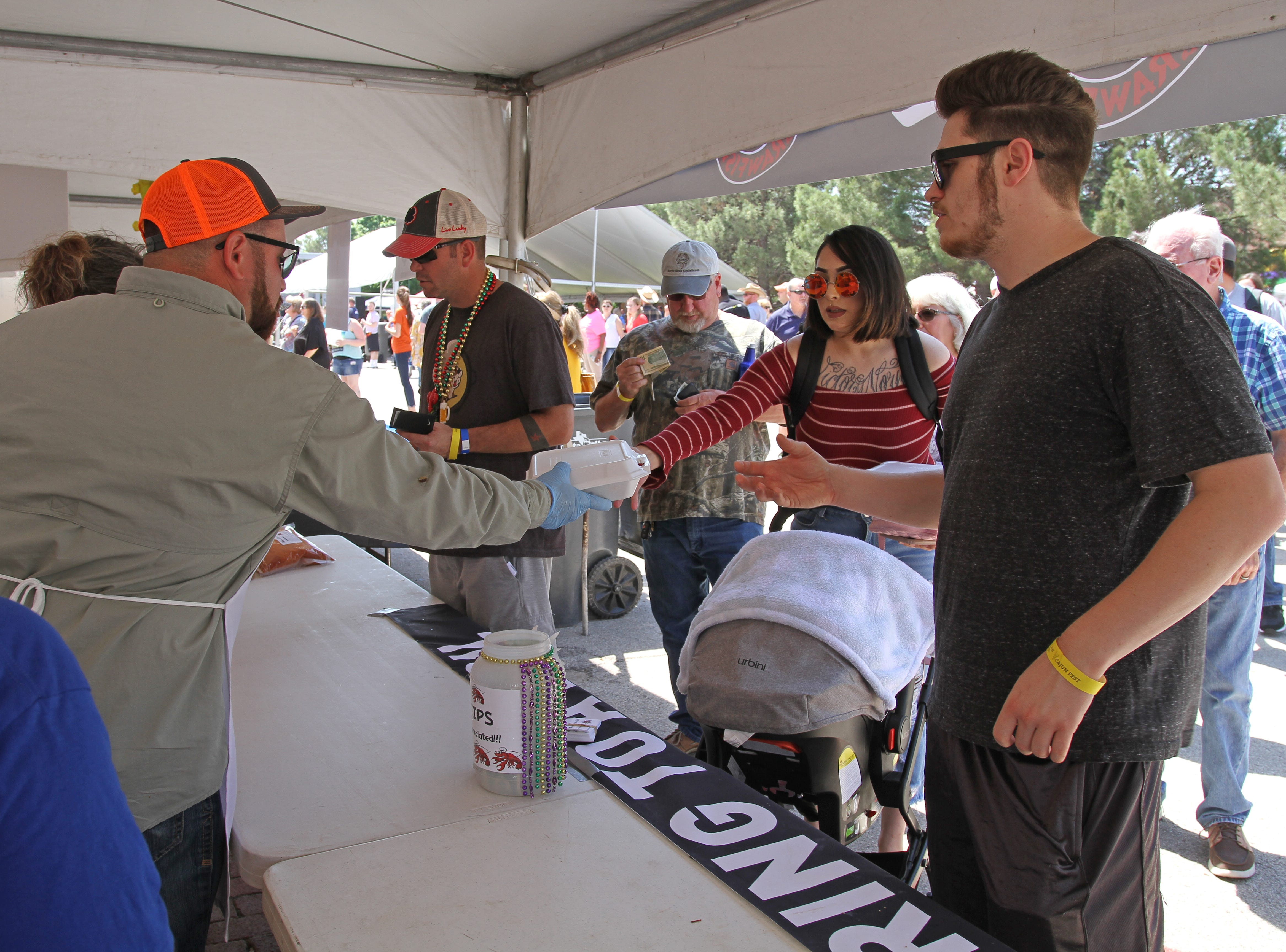 Poeple purchase boxes of crawfish at Cajun Fest Saturday, April 27, 2019, at 10th and Ohio downtown.