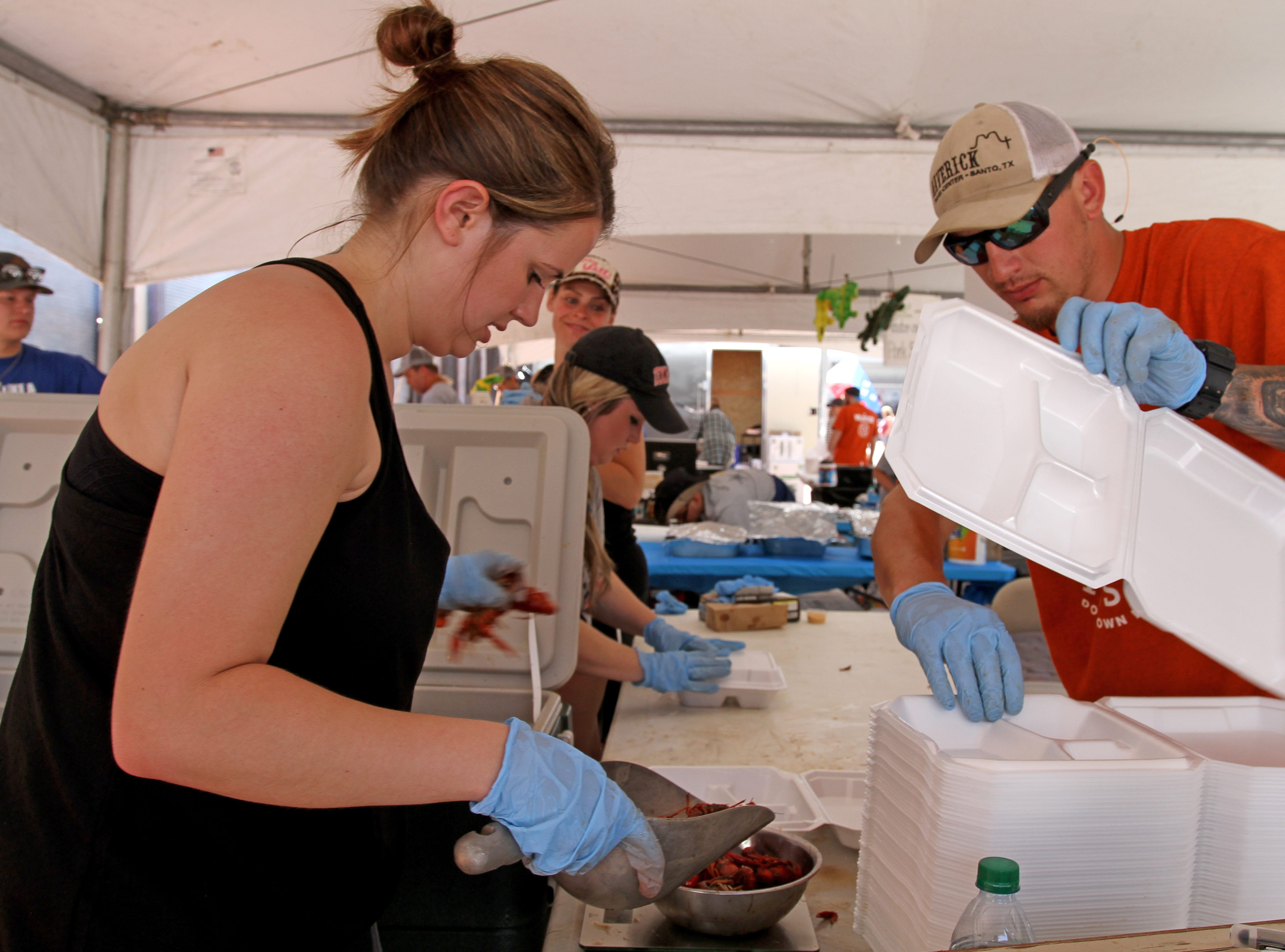 Alexis. left, and Chad Michalski work on serving crawfish at Cajun Fest Saturday, April 27, 2019, at 10th and Ohio downtown.