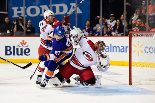 Second round: Hurricanes goalie Petr Mrazek is knocked over by Islanders forward Anders Lee during the second period in Game 1, wiping out a goal. The Hurricanes won 1-0 in overtime.