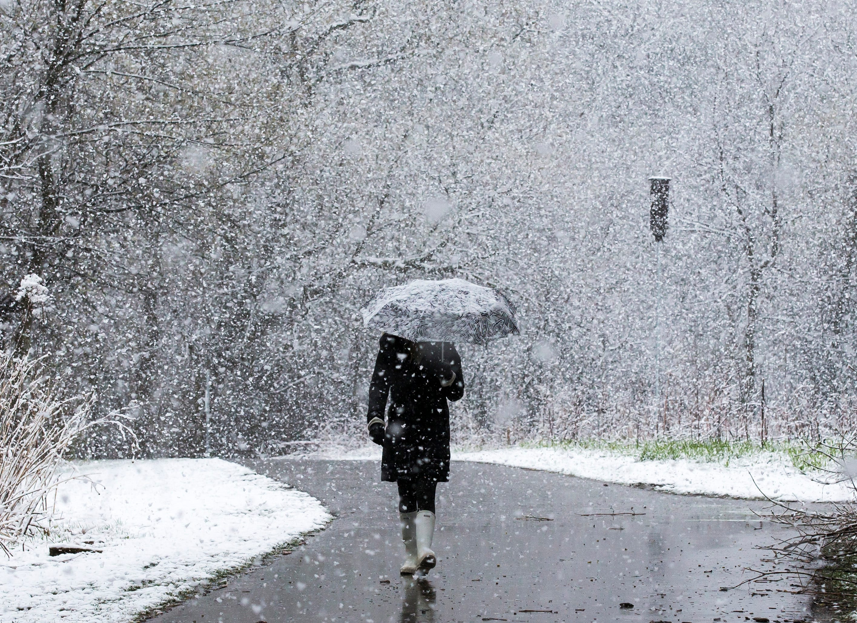 Jodi Frisk is surrounded by snowflakes while walking along a paved path near the Quarry Hill Nature Center on Saturday, April 27, 2019, in Rochester, Minn.