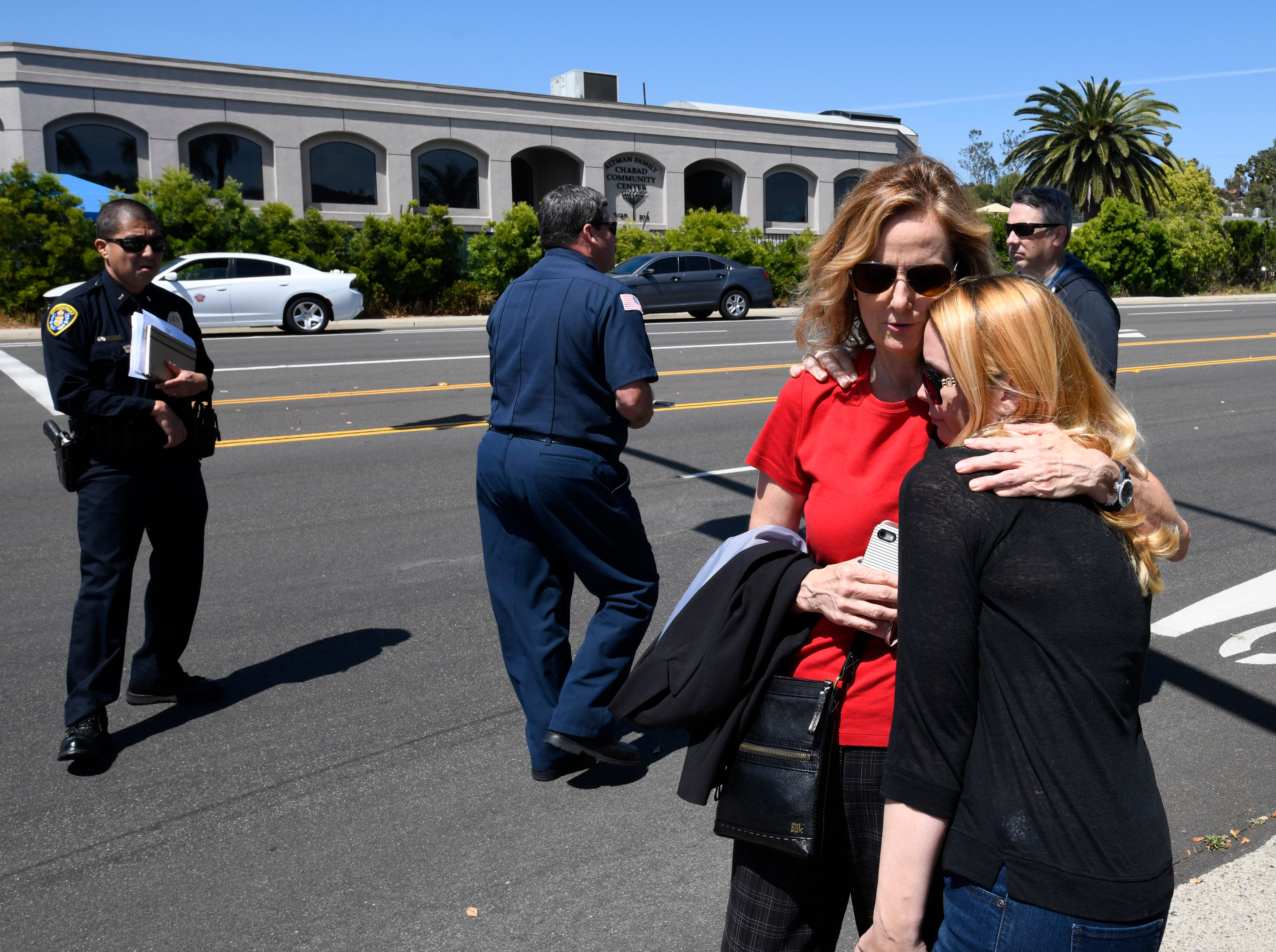 Jessica Parks, right, hugs Tina White outside of the Chabad of Poway Synagogue Saturday, April 27, 2019, in Poway, Calif.