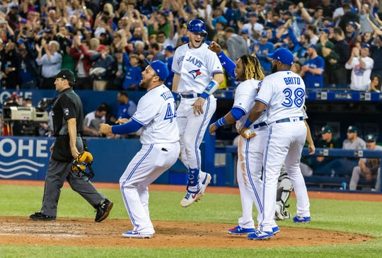 The Blue Jays Danny Jansen (9), Rowdy Tellez (44), Socrates Brito (38) and  Vladimir Guerrero Jr. (27) celebrate their walk-off win against the A's.