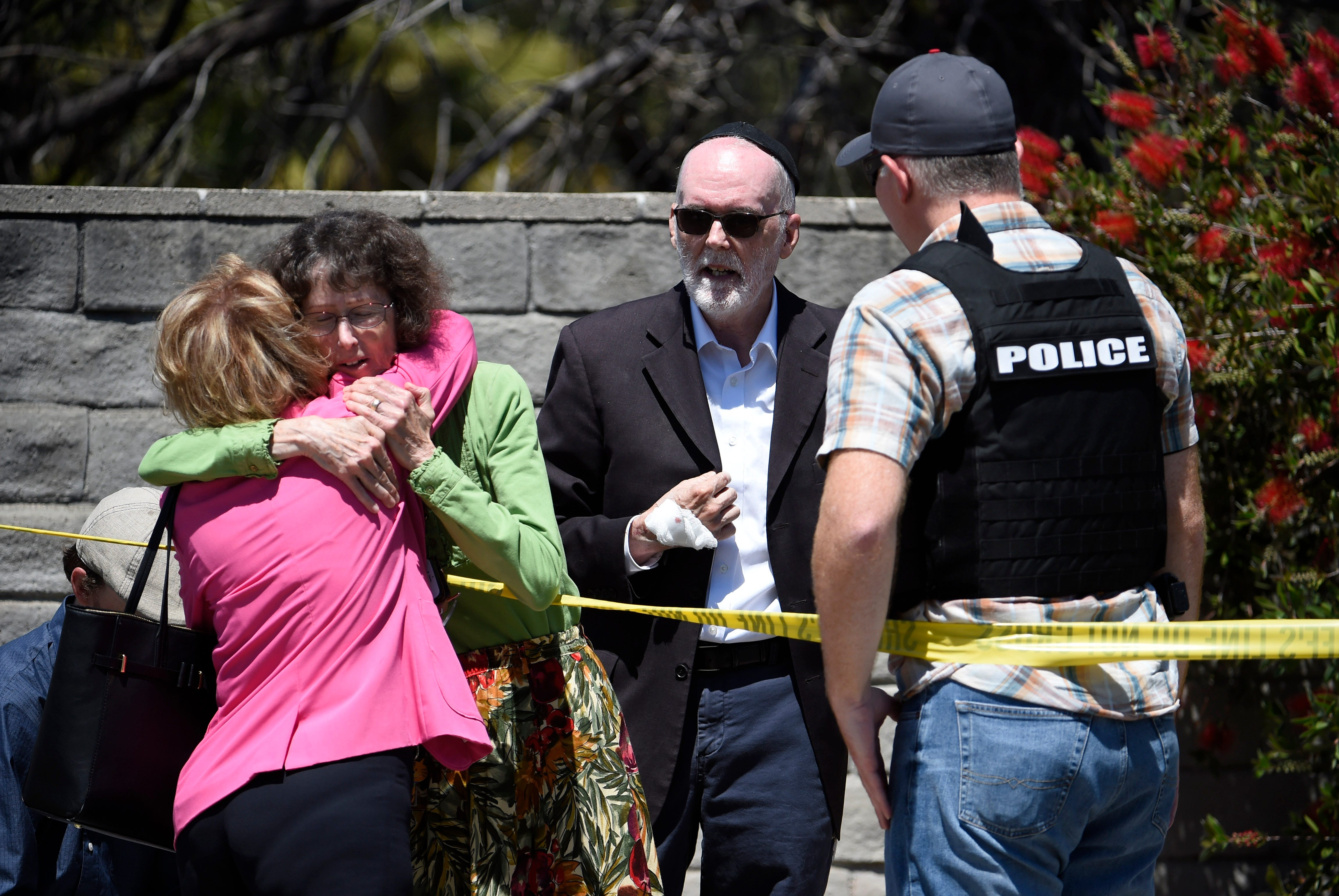 Two people hug as another talks to a San Diego County Sheriff's deputy outside of the Chabad of Poway Synagogue Saturday, April 27, 2019, in Poway, Calif. Several people have been shot and injured at a synagogue in San Diego, California, on Saturday, said San Diego County authorities.