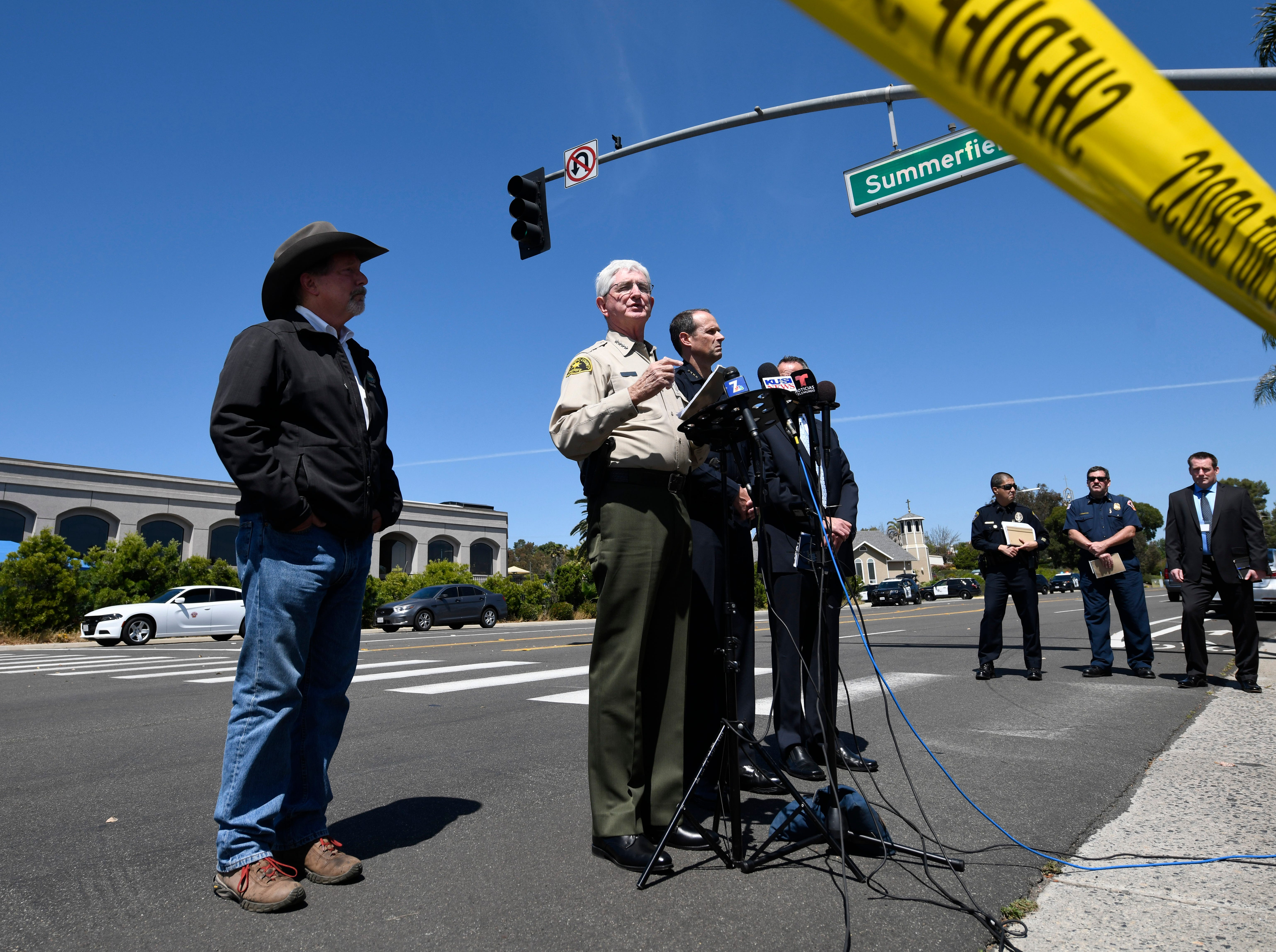 San Diego County Sheriff Bill Gore, center, speaks at a news conference held outside of the Chabad of Poway Synagogue Saturday, April 27, 2019, in Poway, Calif. One person was killed and three injured in a shooting at the synagogue.