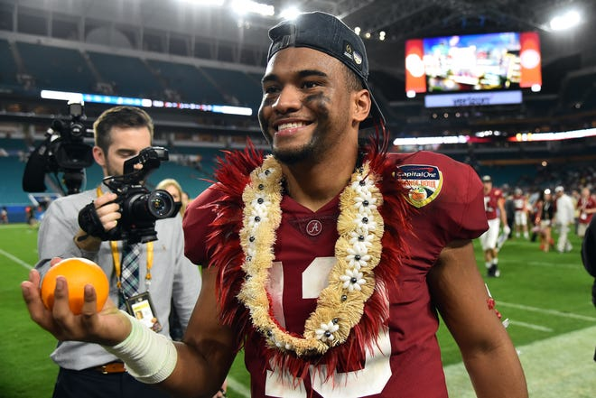 Alabama Crimson Tide quarterback Tua Tagovailoa (13) celebrates with an orange after defeating the Oklahoma Sooners in the 2018 Orange Bowl college football playoff semifinal game at Hard Rock Stadium.