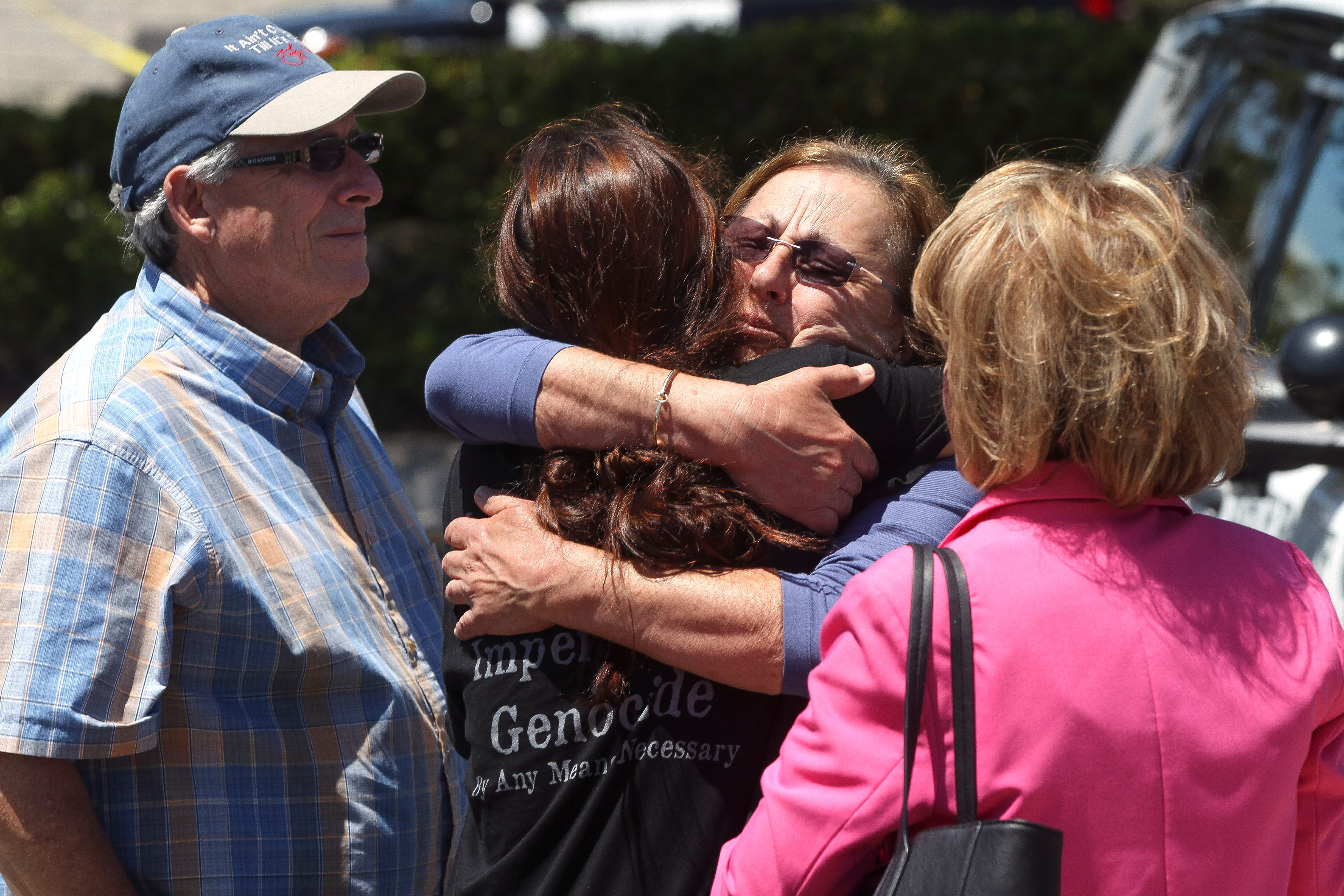 Members of the Chabad synagogue hug as they gather near the Altman Family Chabad Community Center, Saturday, April 27, 2019 in Poway, California.