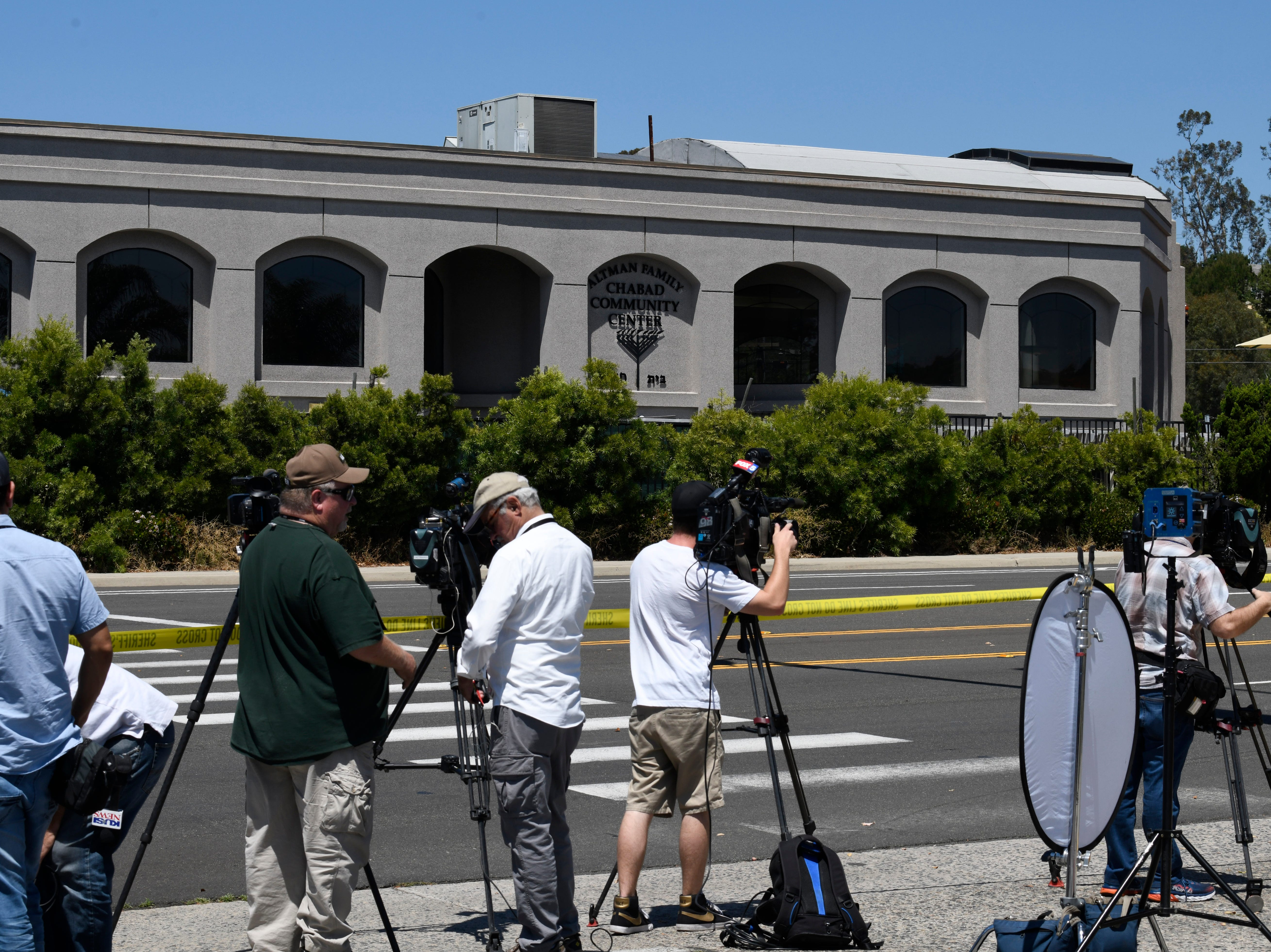 Television cameras film the outside of the Chabad of Poway Synagogue Saturday, April 27, 2019, in Poway, Calif.