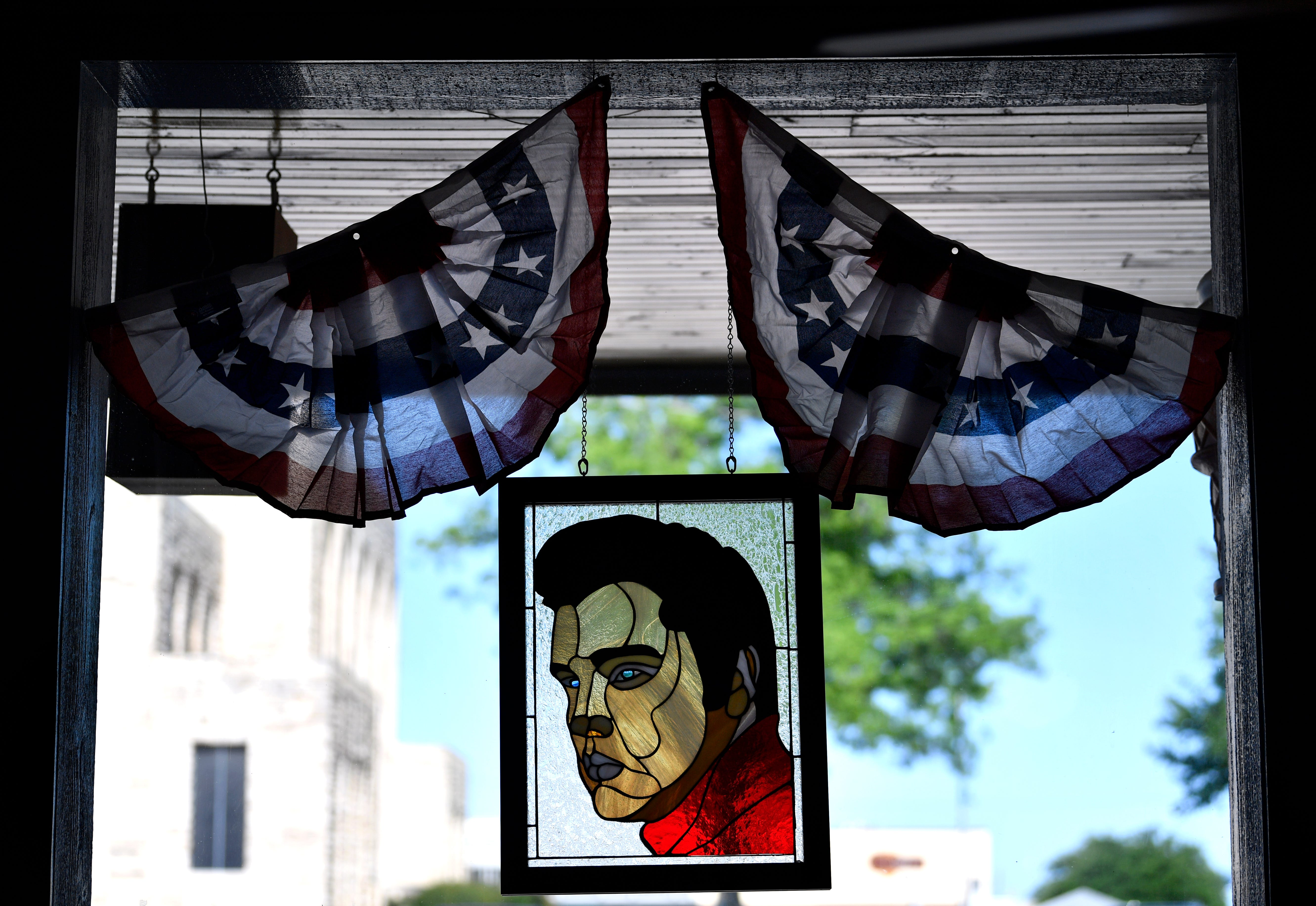 A stained glass portrait of Elvis Presley hangs in the wind of the Soda Shop.