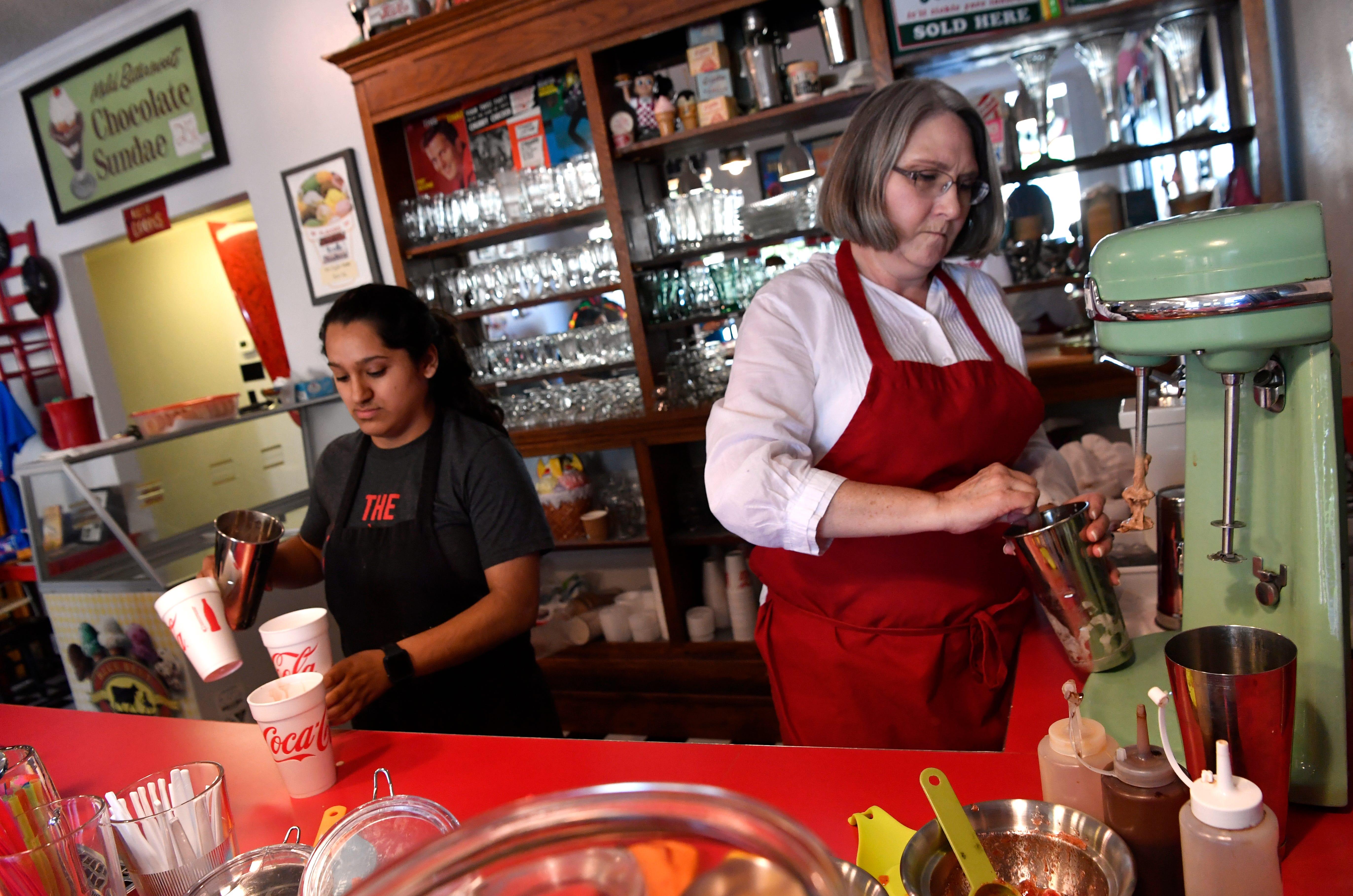 Deana Peltz (right) and Sofia Jimenez make shakes for customers Friday at the Soda Shop in Comanche. The ice cream shop is run by the non-profit Revitalize Comanche.