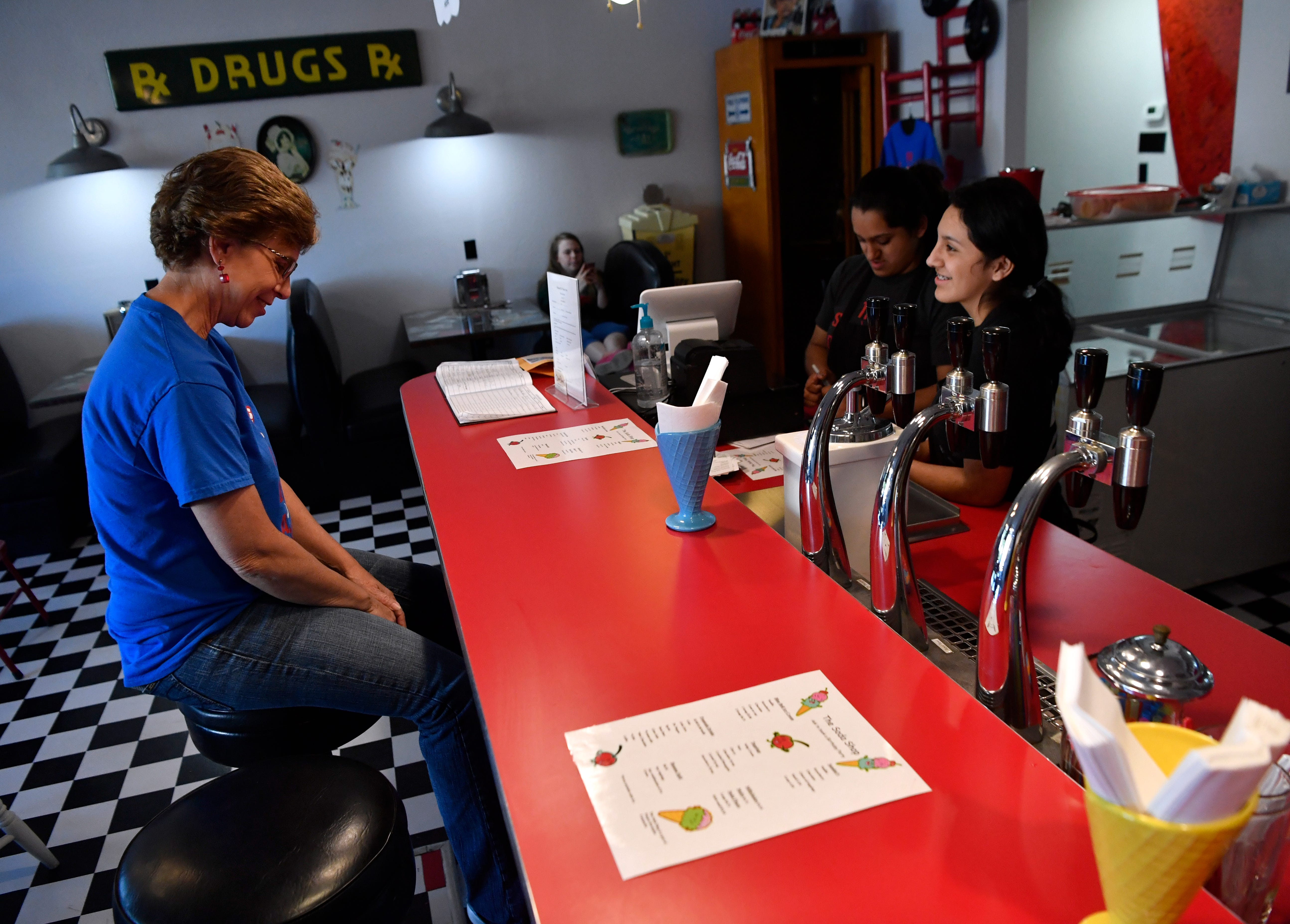 Kristi Taylor, the president of Revitalize Comanche, chats Friday with sisters Luisa and Sofia Jimenez inside the Soda Shop.