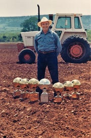An 1989 photo of Stanley Whisenhunt brings to mind two things: he looks a bit like Garth Brooks, and with just seven of many basketball trophies, he easily is a man outstanding in his field.