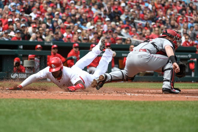 St. Louis Cardinals left fielder Marcell Ozuna (23) slides into home plate to score a run against the Cincinnati Reds during the fourth inning at Busch Stadium.